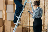 Fotografie Businesswoman writing in clipboard while loader man standing on a ladder