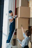 Photo Businesswoman giving instructions to delivery man on a ladder
