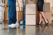 Fotografia Donna di affari e consegna uomo in piedi dalla pila di scatole di cartone