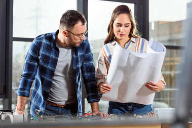 Woman showing project blueprint to male engineer