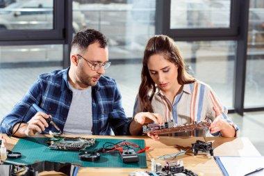 Man assisting woman in circuit board repair