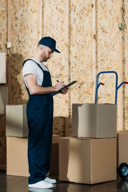 Loader man filling cargo declaration by delivery cart