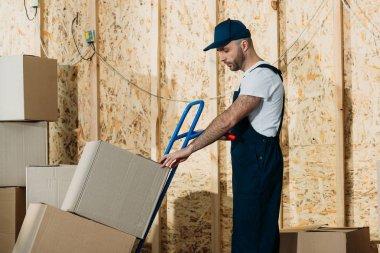 Loader man adjusting cardboard boxes on delivery cart
