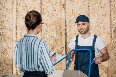 Smiling delivery man with delivery cart looking at businesswoman with clipboard