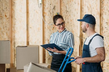 Delivery man and businesswoman filling checklist by stacks of boxes