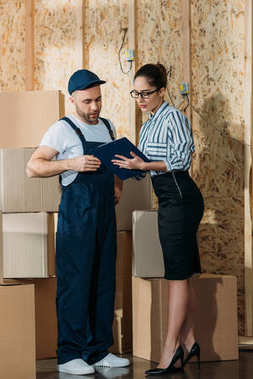 Delivery man and businesswoman looking at cargo declaration by stacks of boxes