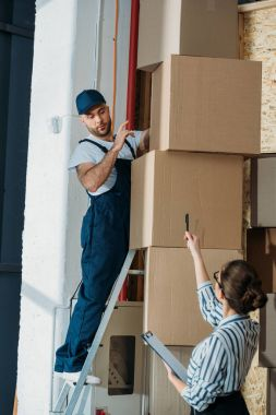 Businesswoman giving instructions to delivery man on a ladder