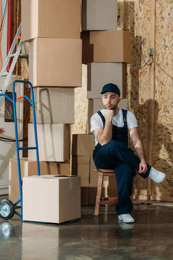 Resting delivery man sitting by stacks of boxes