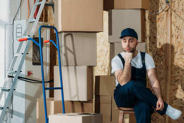 Bored delivery man waiting by stacks of boxes