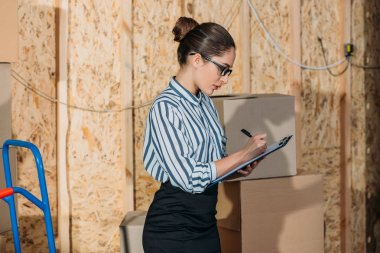 Businesswoman with clipboard filling cargo declaration