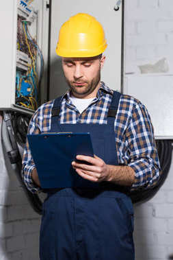 Electrician filling checklist of power line maintenance