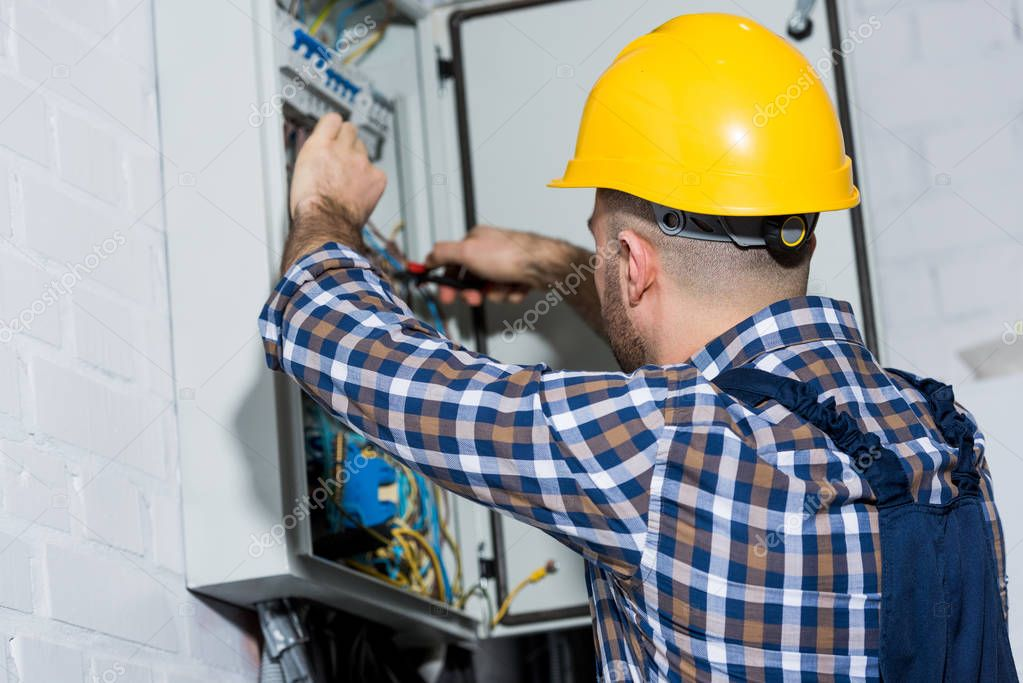 Male electrician checking wires in electrical box