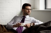Fotografie Image of businessman in glasses sitting with cup of coffee
