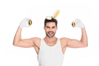 Man with bunny ears showing muscles and holding golden eggs isolated on white, easter concept