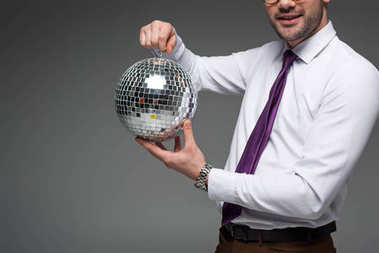 Cropped view of businessman showing glass disco ball isolated on grey