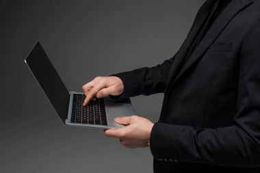 Partial view of businessman holding laptop in hands isolated on grey