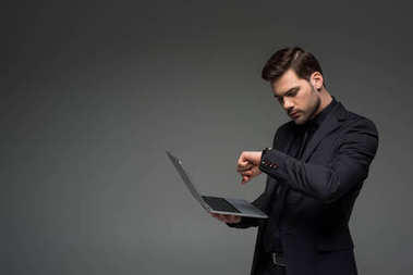 Businessman looking at wristwatch with laptop in hand isolated on grey