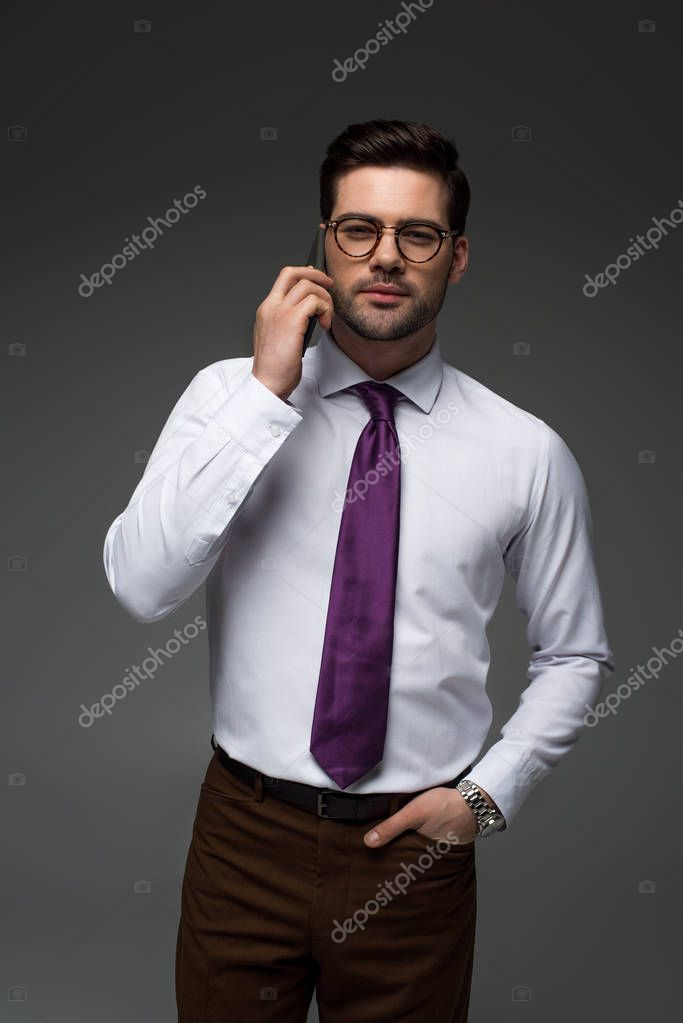 Smiling businessman in glasses talking on smartphone isolated on grey
