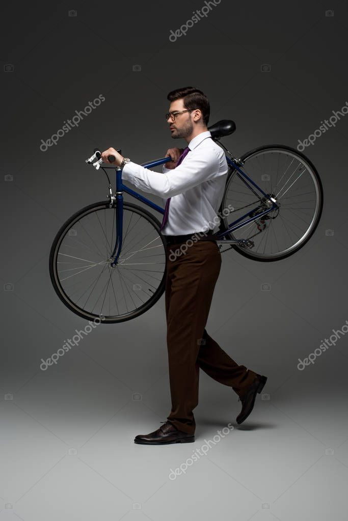 Side view of stylish businessman carrying bicycle on grey