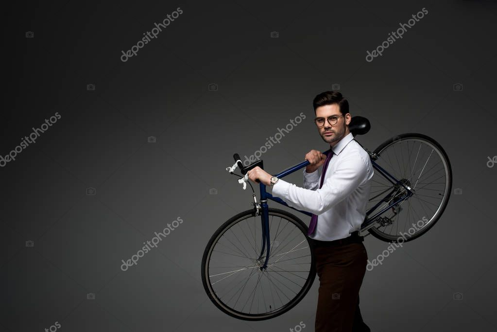 Young businessman in glasses holding bicycle in hands isolated on grey