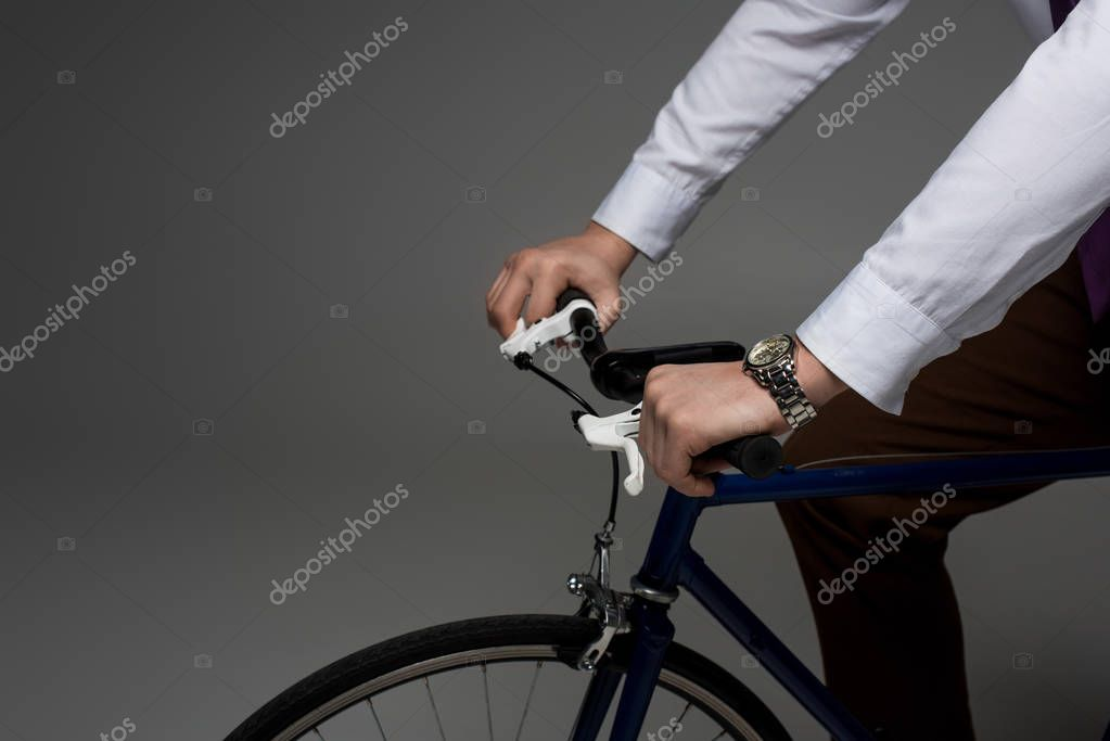 Partial view of businessman riding on bicycle isolated on grey