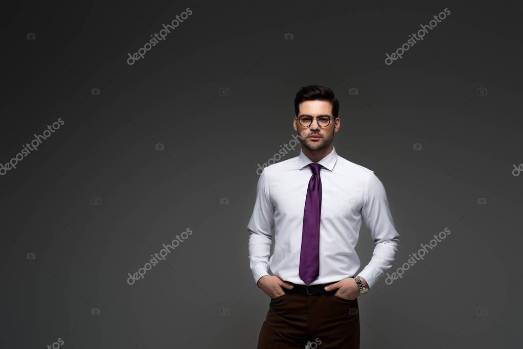 Businessman in glasses standing with fingers in pockets isolated on grey