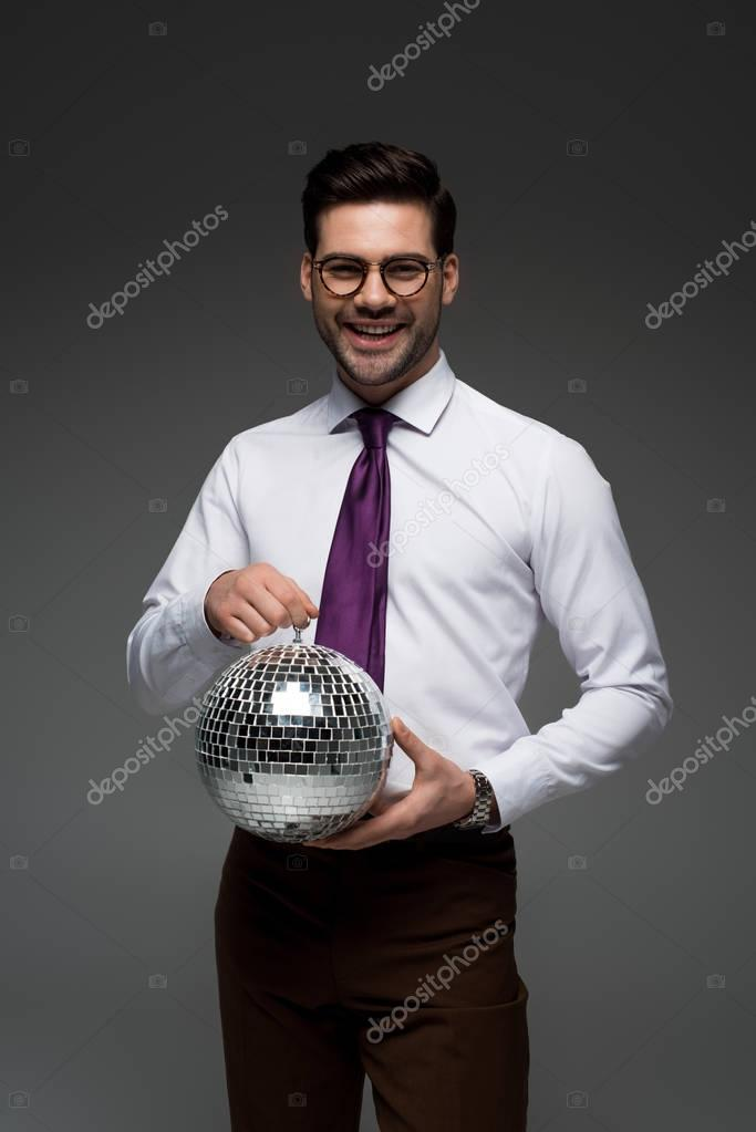 Smiling businessman holding glass disco ball isolated on grey