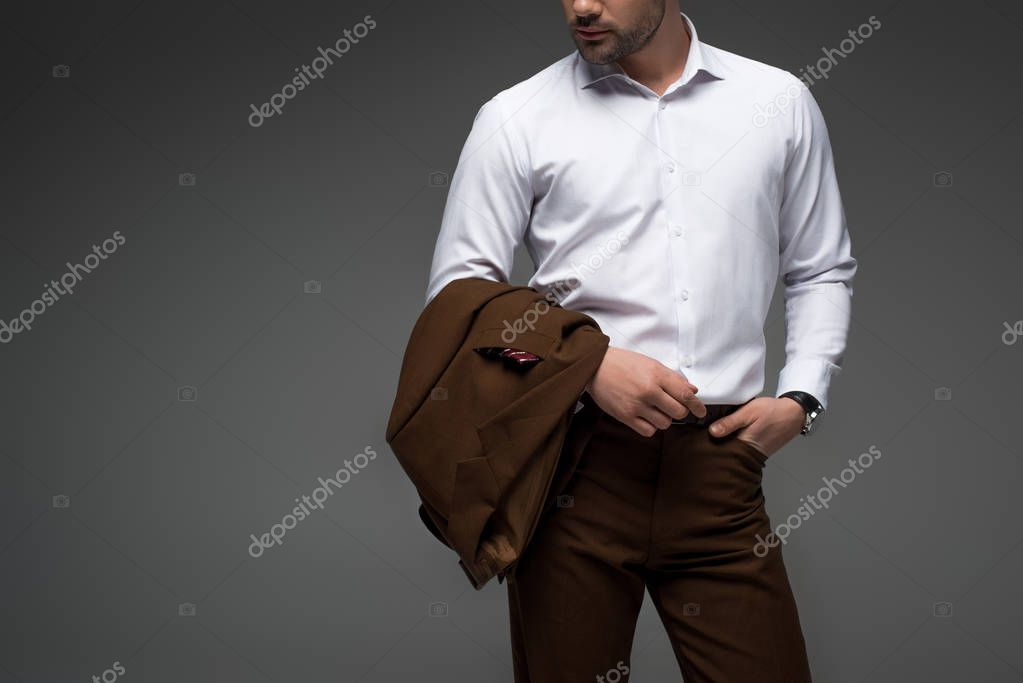 Cropped view of businessman with fingers in pocket on grey