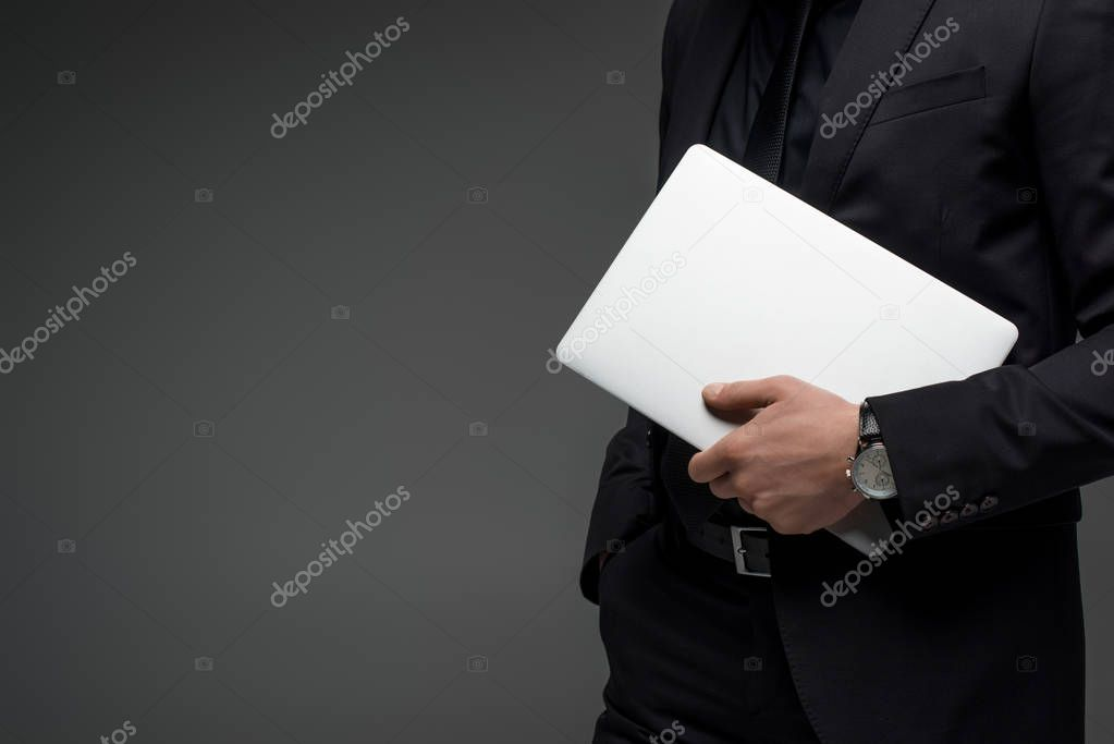 Partial view of businessman holding laptop in hand isolated on grey