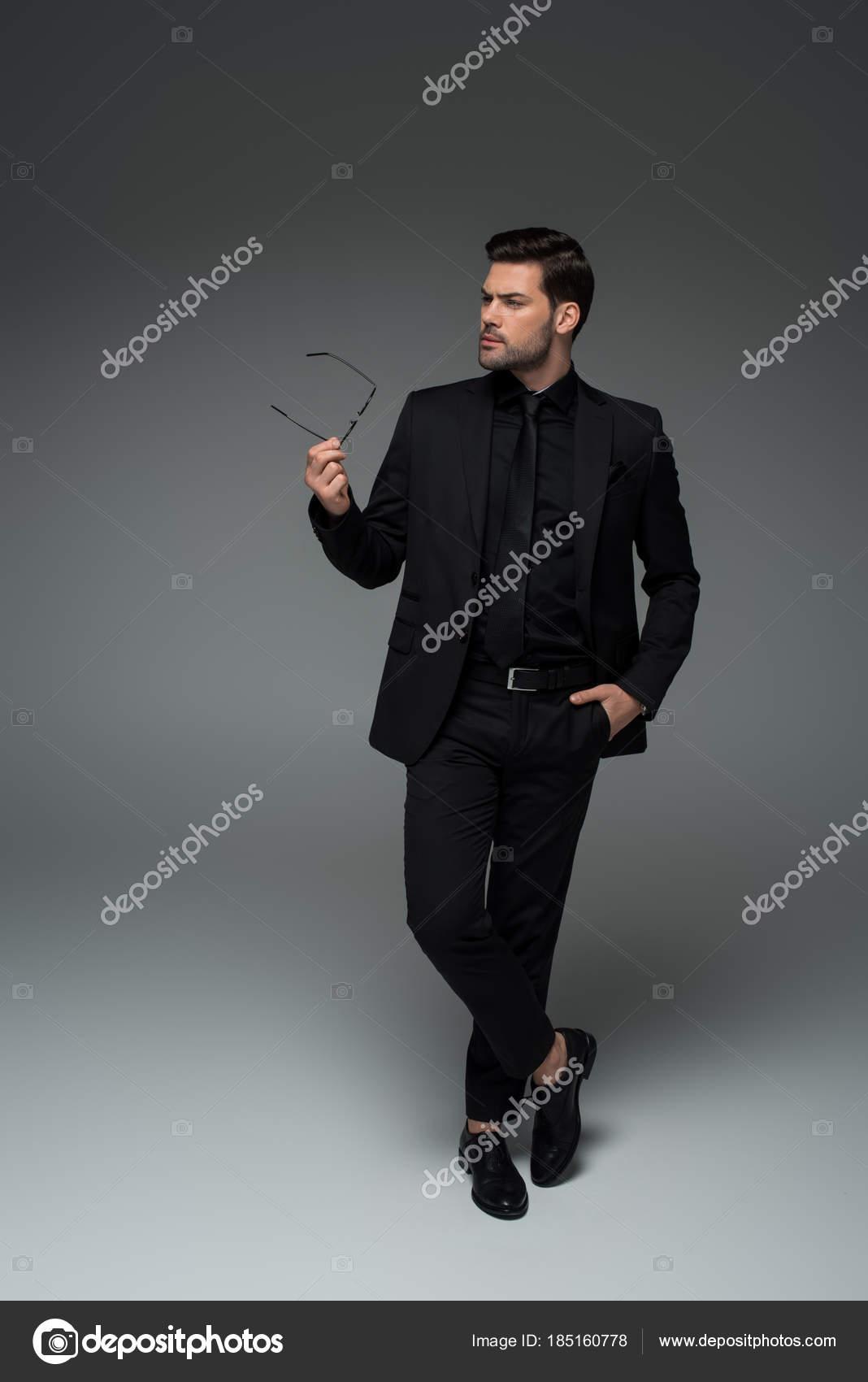 Hombre Elegante Traje Negro Posando Con Vasos Mano Gris — Foto de Stock e0aca1a1944