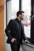 Side view of young businessman looking from window