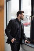 Boční pohled na mladý podnikatel při pohledu z okna