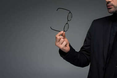 Partial view of stylish man holding glasses isolated on grey