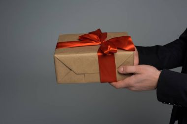 Closeup view of gift box in male hands isolated on grey, international womens day concept