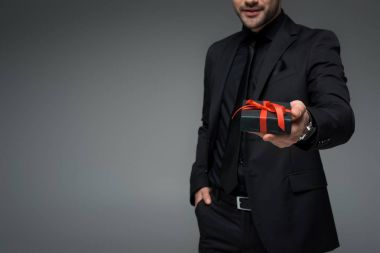 Cropped image of young man in suit holding gift box isolated on grey, international womens day concept