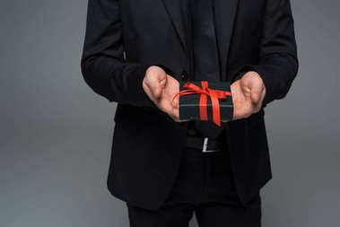 Partial view of male hands holding gift box isolated on grey, international womens day concept