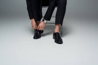 Partial view of stylish man tying shoelaces on grey