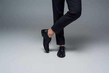 Partial view of male legs in black formal shoes on grey