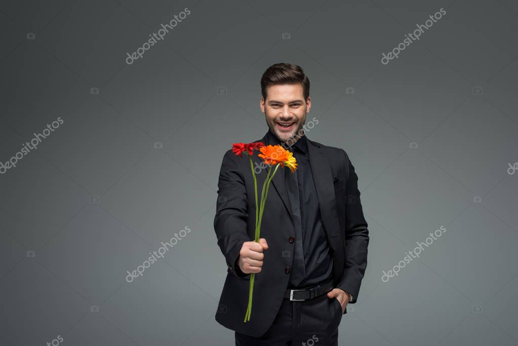 Young man with bouquet of flowers isolated on grey, international womens day concept