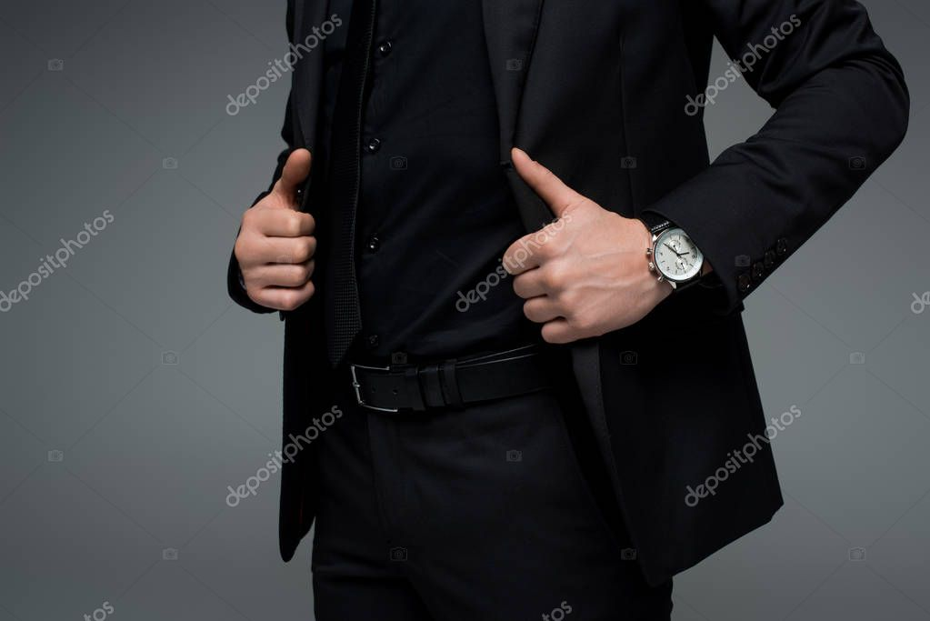 Partial view of male hands holding jacket isolated on grey