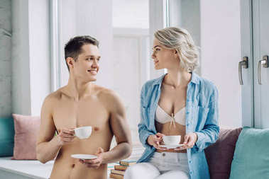 happy sexy couple sitting on windowsill with cups of coffee at home
