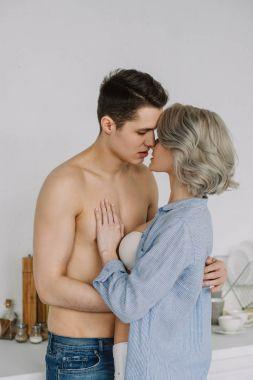 seductive half naked couple kissing at kitchen