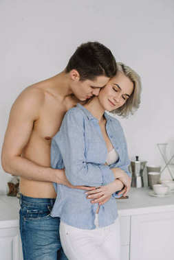 seductive young couple hugging at kitchen