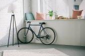 Fotografie Fahrrad neben Fensterbank im Wohnzimmer