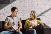 Fotografie lächelnde paar Holding Tassen Kaffee und sahen einander zu Hause