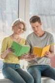 Fotografie couple sitting on windowsill and reading books at home