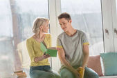 happy girlfriend showing book to boyfriend on windowsill