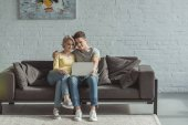 affectionate couple watching movie at laptop at home