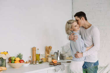 boyfriend hugging and kissing girlfriend at kitchen