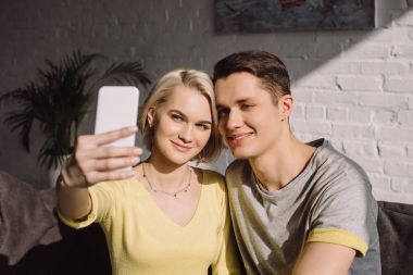 smiling couple taking selfie with smartphone in living room